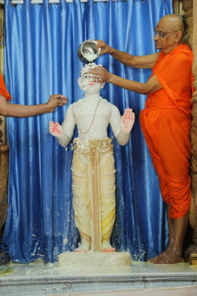 His Divine Holiness Acharya Swamishree bathes Lord Shree Swaminarayan with yougurt
