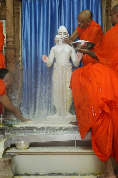 His Divine Holiness Acharya Swamishree bathes Lord Shree Swaminarayan with sugar powder