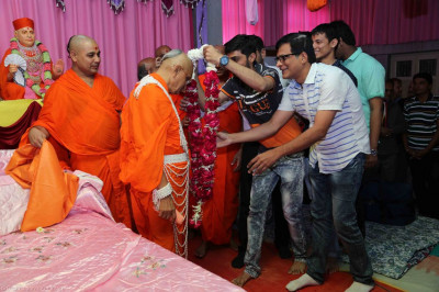 Disciples offer His Divine Holiness Acharya Swamishree a garland of flowers