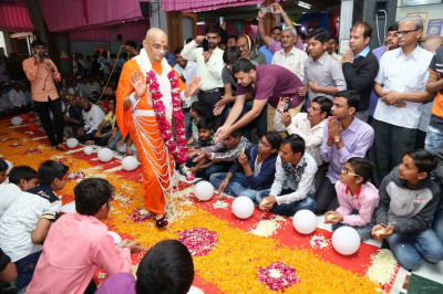 Disciples shower flower petals as His Divine Holiness Acharya Swamishree walks towards the front of the mandir