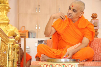 Acharya Swamishree showers flower petals at the lotus feet of the Lord