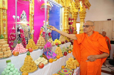 His Divine Holiness Acharya Swamishree offers cake to the Lord