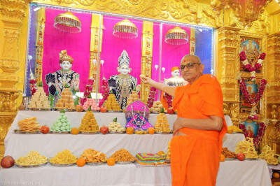 His Divine Holiness Acharya Swamishree offers sweets to the Lord Shree Swaminarayan
