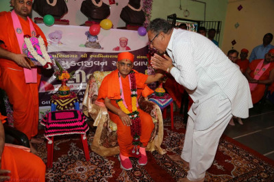 The representatives of the education establishment offer Acharya Swamishree a garland of flowers