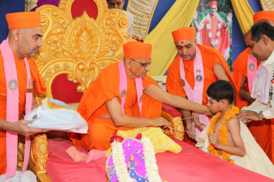 His Divine Holiness Acharya Swamishree places the sacred thread around the young Bhramins