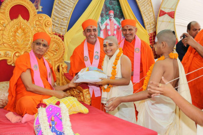 His Divine Holiness Acharya Swamishree presents gifts as a donation to the young Bhramins