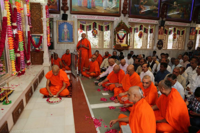 His Divine Holiness Acharya Swamishree showers rose petals at the divine lotus feet of Lord Shree Swaminarayan
