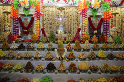 Divine darshan of Lord Shree Swaminarayan dining on sweets and savouries in the form of annakut