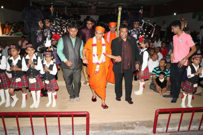 Disciples escort His Divine Holiness Acharya Swamishree to the stage