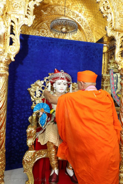 Acharya Swamishree Maharaj puts a garland on Lord Shree Swaminarayan