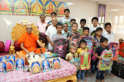 His Divine Holiness Acharya Swamishree blesses young disciples and presents them with new school bags