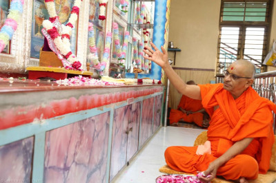 His Divine Holiness Acharya Swamishree showers fragrant flower petals at the divine lotus feet of the Lord