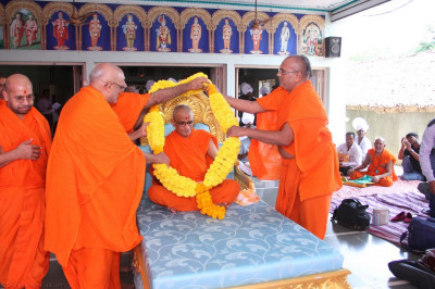 Sants present a huge garland of bright yellow and orange flowers to His Divine Holiness Acharya Swamishree