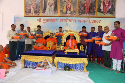 His Divine Holiness Acharya Swamishree blesses disciples offering various gifts to the Lord