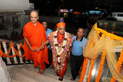 Acharya Swamishree is escorted into the Mandir by sants and disciples