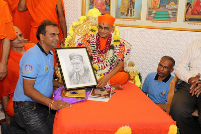 A disciple presents a hand-sketched drawing of Acharya Swamishree to Him