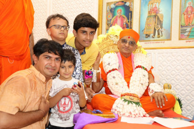 Young disciples present a garland made from cotton to Acharya Swamishree