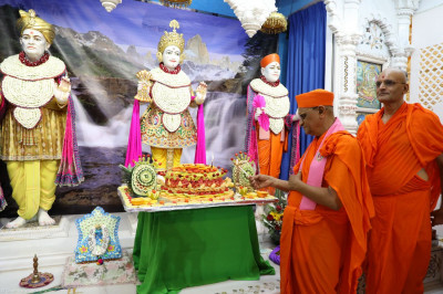 Acharya Swamishree picks some fruit from the intricate carving to offer to Lord Swaminarayanbapa Swamibapa