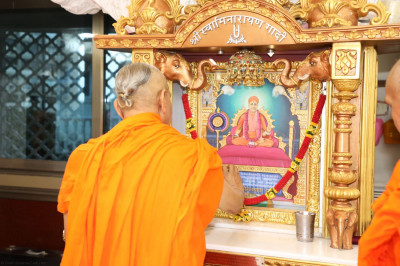 Acharya Swamishree performs poojan to Jeevanpran Shree Muktajeevan Swamibapa seated on Shree Swaminarayan Gadi