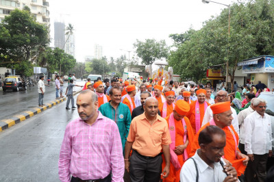 Sants and disciples walk in the procession towards the Mandir