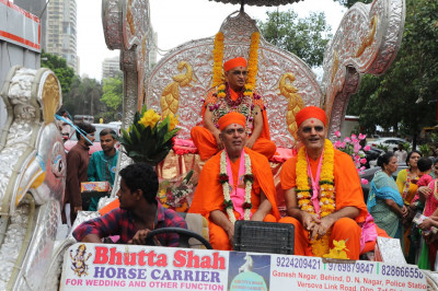 Acharya Swamishree and Mumbai Mandir Sants are seated on the chariot during the procession