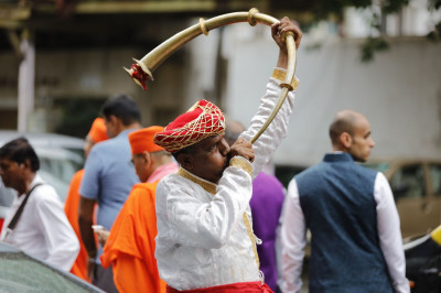 A local musician plays a traditional horn during the procession