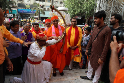 Acharya Swamishree blesses the local musician who played a traditional horn throughout the procession