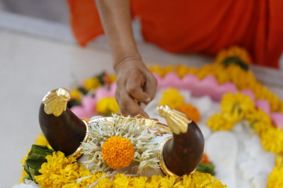 Acharya Swamishree Maharaj installs the divine footprints of Lord Shree Swaminarayan, which are constantly being bathed by a stream of water emerging from the mouth of a sacred cow