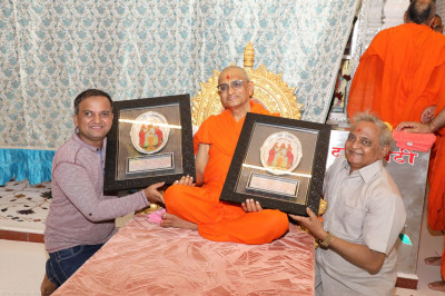 Acharya Swamishree presents mementos to disciples to commemorate the Suvarna Pratishtha (Golden Jubilee - 50th Anniversary) celebrations of Shree Swaminarayan Mandir Mumbai
