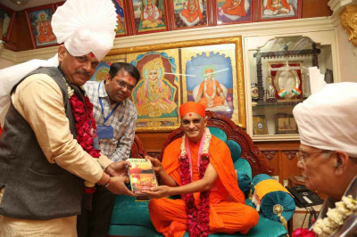 His Divine Holiness Acharya Swamishree presents various publications to the honoured guests
