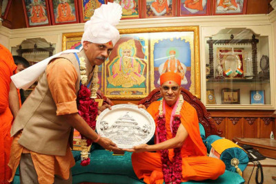 His Divine Holiness Acharya Swamishree presents a momento of Smruti Mandir to the honoured guest