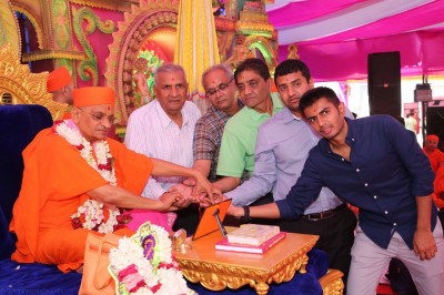 His Divine Holiness Acharya Swamishree performs the scripture recital poojan ceremony with disciples who are the sponsors