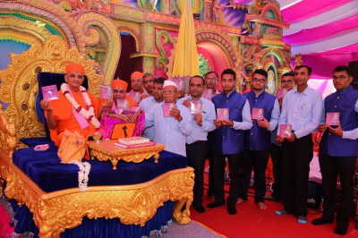 His Divine Holiness Acharya Swamishree officially releases the new scripture Shreeji Sankalpa Murti Sadguru Shree Nirgundasji Swami and presents a copy of the scripture to disciples who have sponsored it