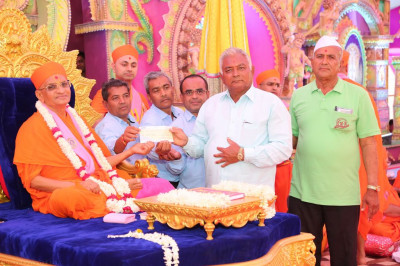 His Divine Holiness Acharya Swamishree presents a cheque to local charitable organisations that look after the welfare of cows and cattle