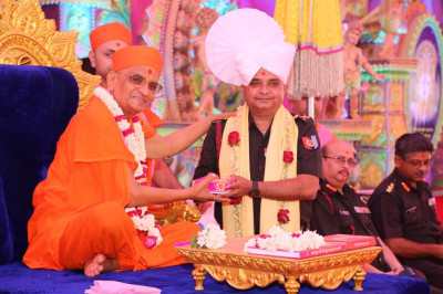 His Divine Holiness Acharya Swamishree blesses the honoured guest and presents a paag, prasad, a shawl and a garland of fresh flowers