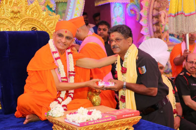 His Divine Holiness Acharya Swamishree blesses the honoured guest and presents prasad, a shawl and a garland of fresh flowers