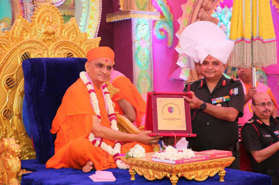 The honoured guest presents a plaque to His Divine Holiness Acharya Swamishree