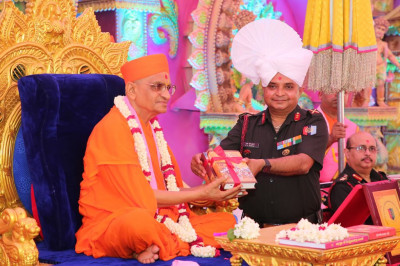 His Divine Holiness Acharya Swamishree presents various divine scriptures and publications to the honoured guest
