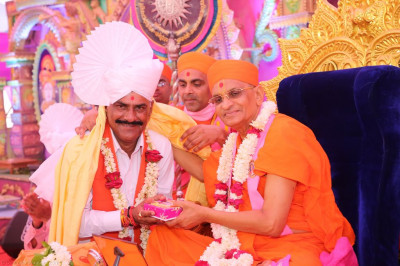 His Divine Holiness Acharya Swamishree presents prasad paag, shawl, garland of fresh flowers and prasad as He blesses the honoured guest