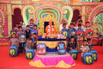 His Divine Holiness Acharya Swamishree blesses young disciples and presents school bags to the primary school children