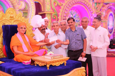 His Divine Holiness Acharya Swamishree presents cheques to various charitable organisations
