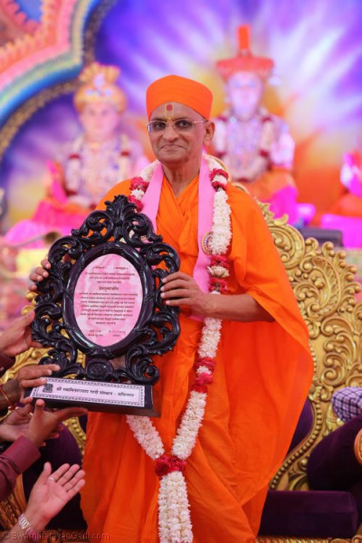 Divine darshan of Acharya Swamishree with the commemorative shield