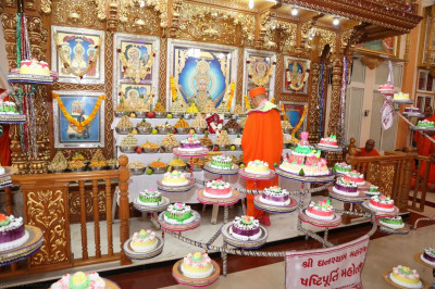 His Divine Holiness Acharya Swamishree cuts a slice of cake