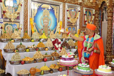 His Divine Holiness Acharya Swamishree offers a slice of cake to Lord Shree Swaminarayan