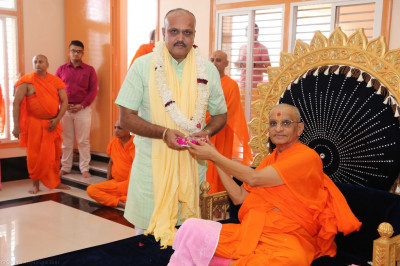 His Divine Holiness Acharya Swamishree presents prasad shawl and prasd to the honoured guest