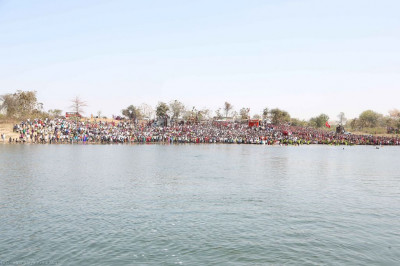 Divine darshan of Acharya Swamishree seated on the boat with thousands of disciples lining the banks of the lake