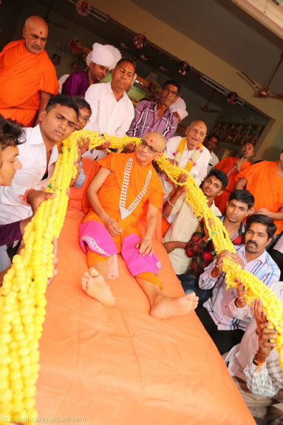 Disciples offer a 75-foot long garland to His Divine Holiness Acharya Swamishree