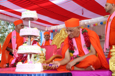 Acharya Swamishree cuts the four-tiered cake