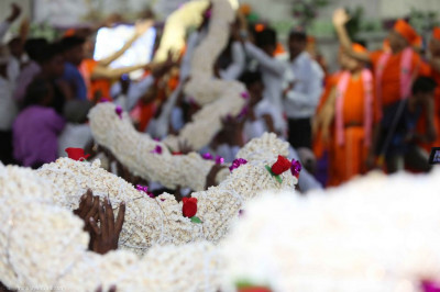 A huge multi-strand garland made of popcorn is offered to Acharya Swamishree