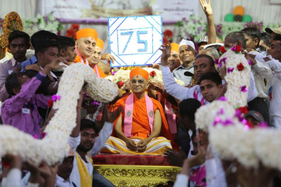 Disciples offer a huge multi-strand garland made of popcorn is offered to His Divine Holiness Acharya Swamishree